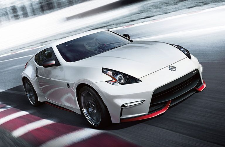 Exterior view of a white 2017 Nissan 370Z driving on an empty race track