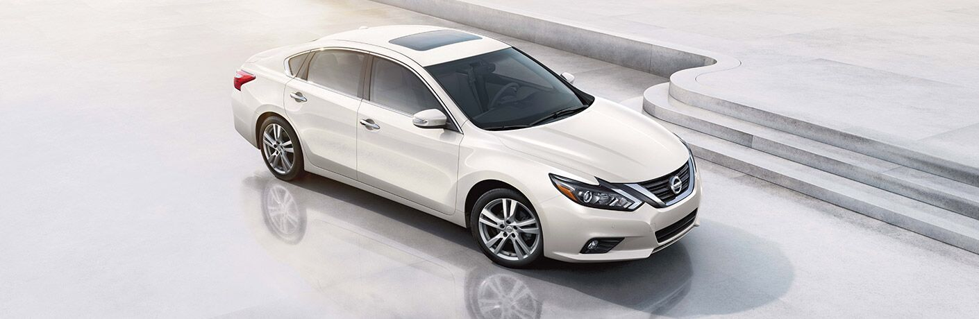 Exterior view of a white 2017 Nissan Altima parked inside a white showroom next to a small flight of stairs