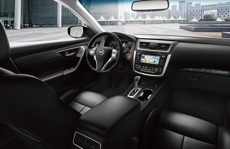Interior view of the black seating, steering wheel, and touchscreen of a 2017 Nissan Altima
