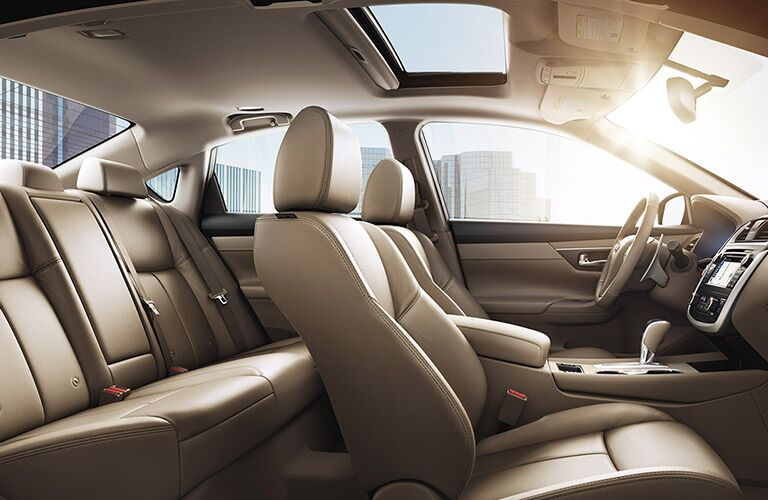 Interior view of the tan front and rear seating of a 2017 Nissan Altima
