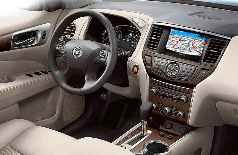 Interior view of the front seating area inside a 2017 Nissan Pathfinder highlighting the steering wheel and navigation system