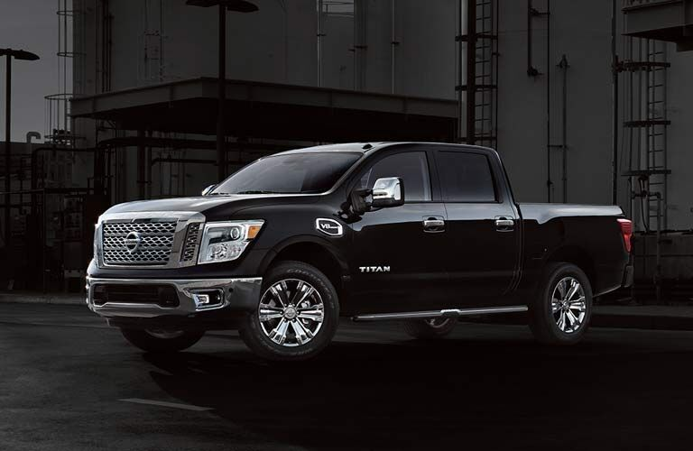 Exterior view of a black 2017 Nissan Titan parked near a warehouse