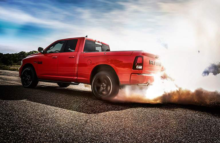 Exterior view of an orange 2017 RAM 1500 doing a burnout in a parking lot