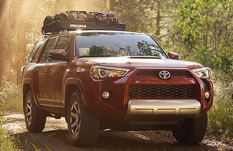 Exterior view of a red 2017 Toyota 4Runner parked in the woods