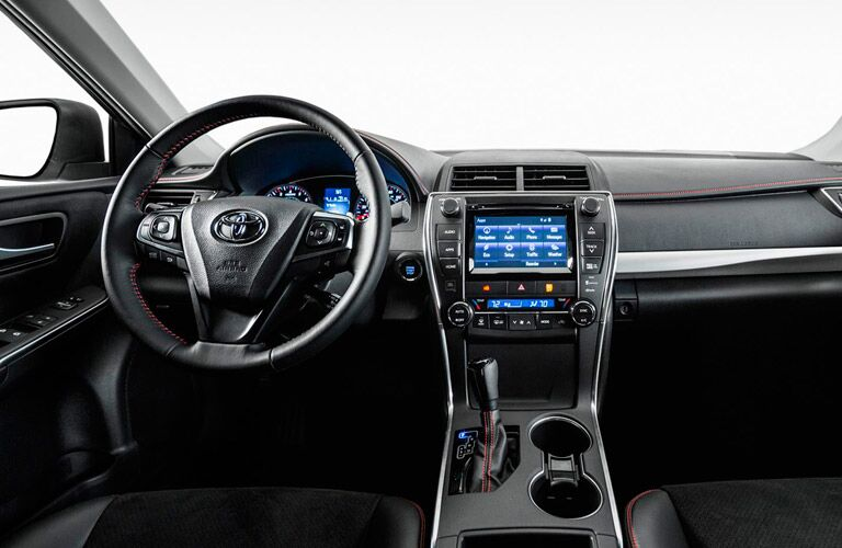 Interior view of the black steering wheel and touchscreen inside a 2017 Toyota Camry