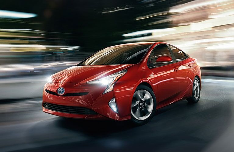 Exterior view of a red 2017 Toyota Prius driving down a city street