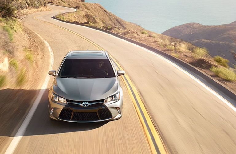 Exterior view of the front of a silver 2017 Toyota Camry driving down a coastal highway