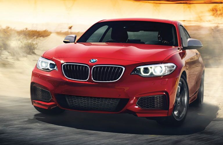 Exterior view of a red 2017 BMW 2 Series coupe driving around a desert race track
