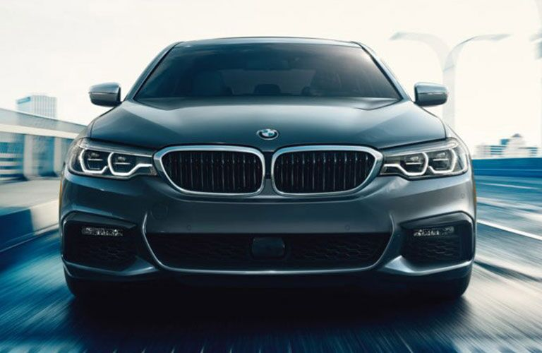 Exterior view of a grey 2017 BMW 5 Series sedan driving down a city street