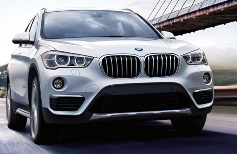 Exterior view of a silver 2017 BMW X model SAV driving down a road