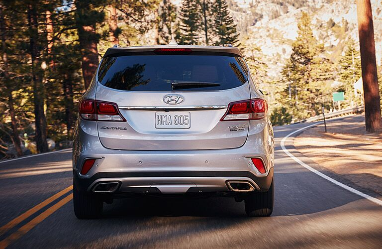 Exterior view of the rear of a silver 2017 Hyundai Santa Fe driving down a two lane road