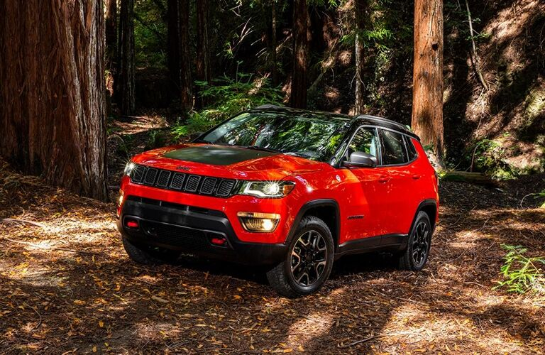 Exterior view of an orange 2017 Jeep Compass parked in the woods