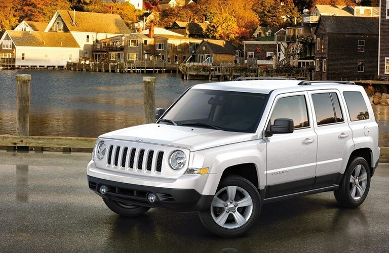Exterior view of a silver 2017 Jeep Patriot parked in a parking lot near a body of water