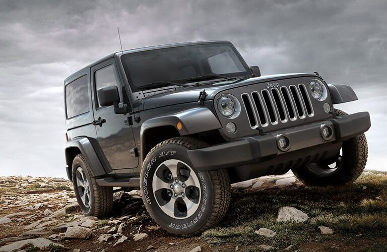 Exterior view of a black 2017 Jeep Wrangler parked on rocky terrain