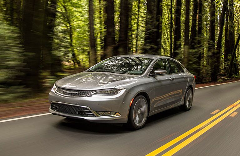 Exterior view of a grey 2017 Chrysler 200 driving down a two-lane road