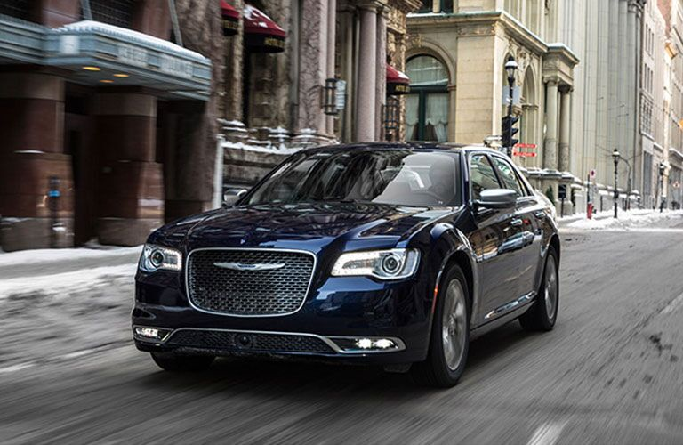 Exterior view of a blue 2017 Chrysler 300 driving down a city street