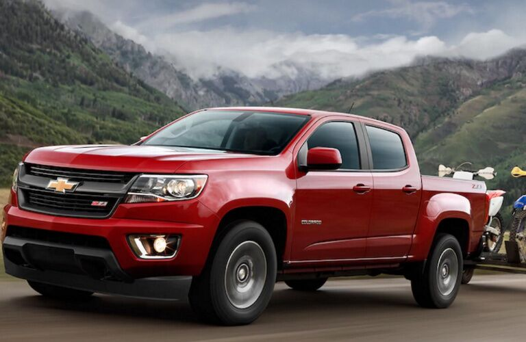 Exterior view of a red 2017 Chevrolet Colorado towing a trailer with dirt bikes down the highway