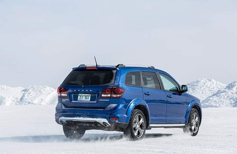 Exterior view of the rear of a blue 2017 Dodge Journey parked in the snow