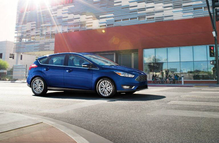 Exterior view of a blue 2017 Ford Focus stopped at a crosswalk in the city