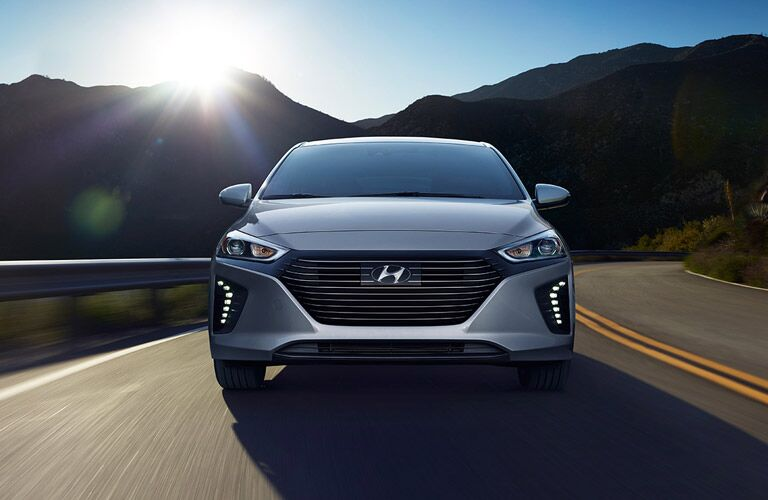Exterior view of a silver 2017 Hyundai IONIQ driving down a two-lane highway