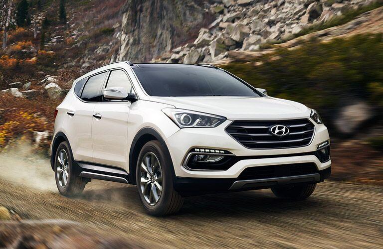 Exterior view of a white 2017 Hyundai Santa Fe Sport driving down a gravel road