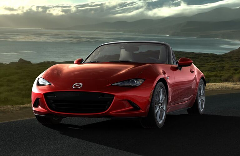 Exterior view of the front of a red 2017 Mazda MX-5 Miata parked on a country road
