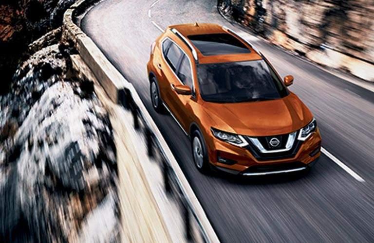 orange 2017 Nissan Rogue driving along mountain road