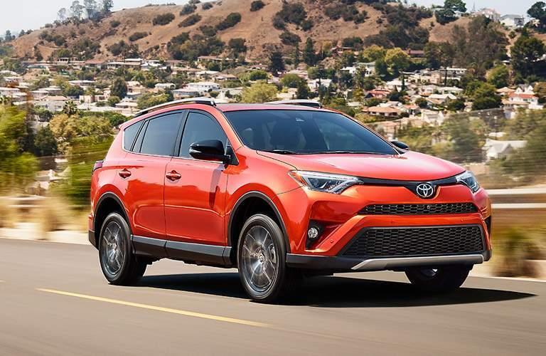 orange 2017 Toyota RAV4 driving near hills