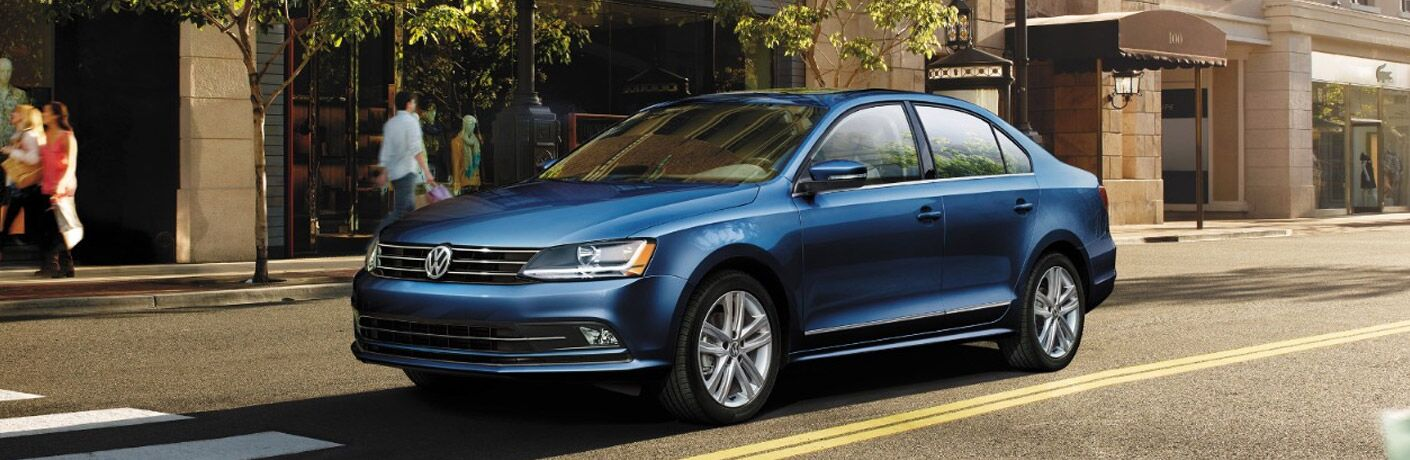 Exterior view of a blue 2017 Volkswagen Jetta driving down a city street