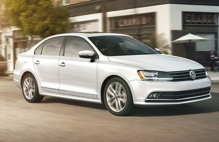 Exterior view of white 2017 Volkswagen Jetta driving down a city street