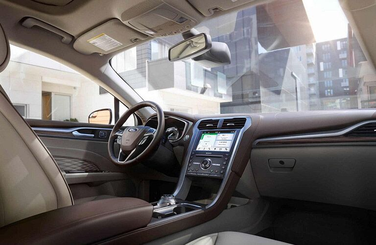 View of tan interior of 2018 Ford Fusion and steering wheel and touch screen
