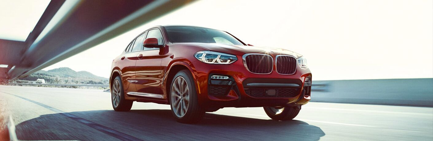 Exterior view of a red 2019 BMW X6 driving down the highway