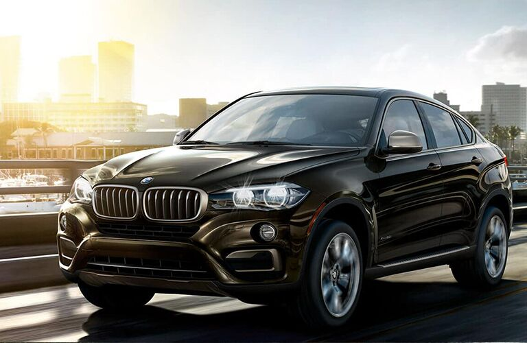 Exterior view of a black 2019 BMW X6 driving over a bridge in the city