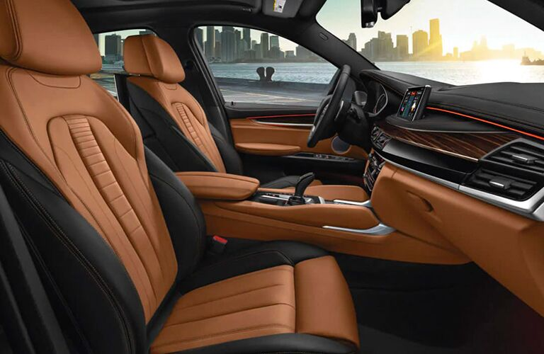 Interior view of the front seating area inside a 2019 BMW X6 that highlights the orange and black seating and steering wheel