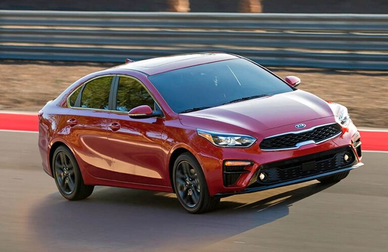 Exterior view of a red 2019 Kia Forte driving around a closed racetrack