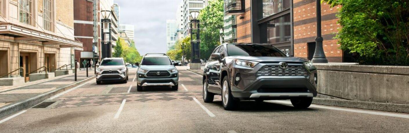 Exterior view of three Toyota RAV4 models driving down a city street