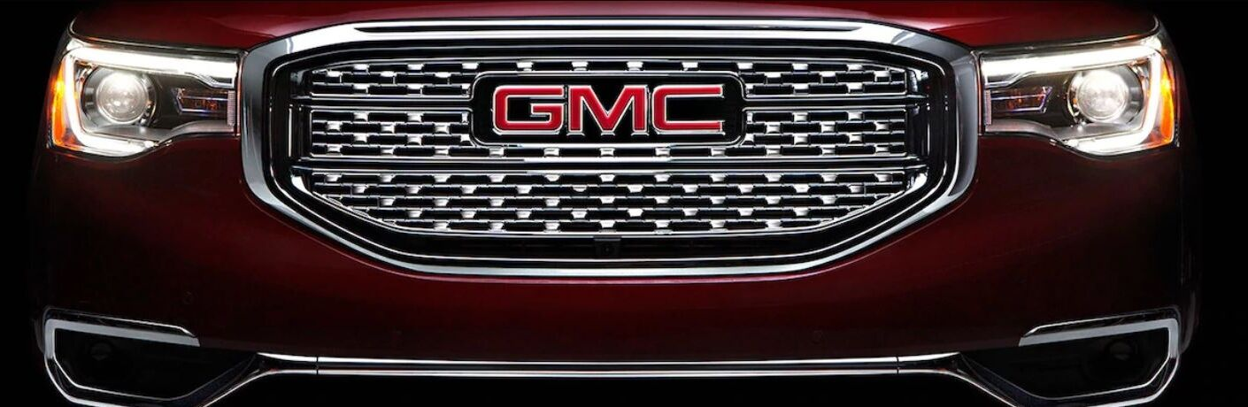 Closeup view of the GMC badge on the front grille of a red GMC vehicle