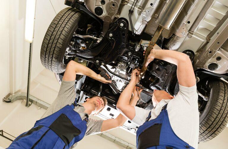 Two Automotive Technicians Servicing a Vehicle