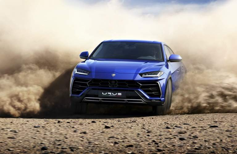 Lamborghini Urus blue front view sliding through sand