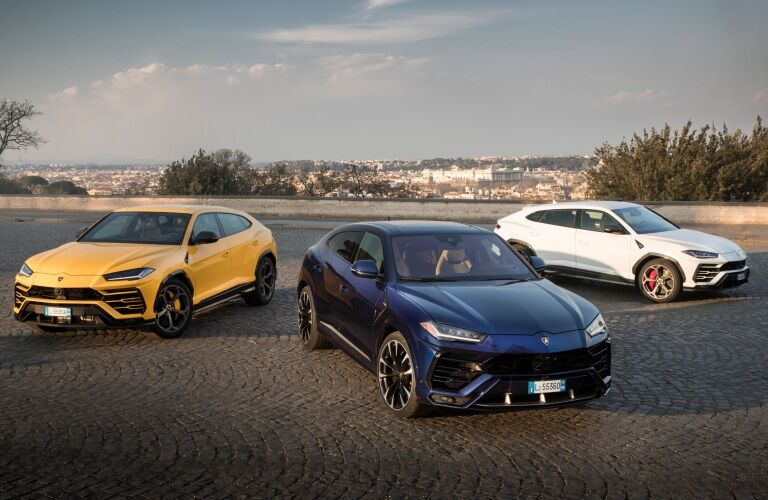 Lamborghini Urus in yellow blue and white side by side front view