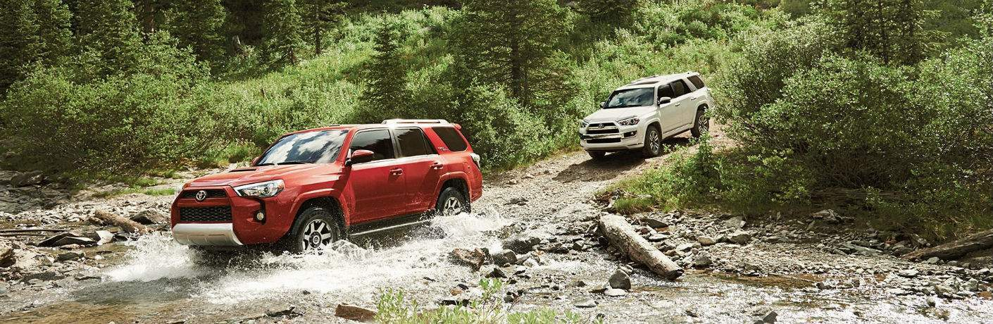 Red and White 2018 Toyota 4Runner Models Fording a River in the Woods