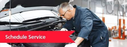 Mechanic Working Under the Hood of a Car with a Red Schedule Service Banner