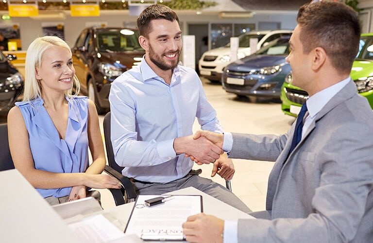 Couple Shaking Hands with Car Salesman in Dealership