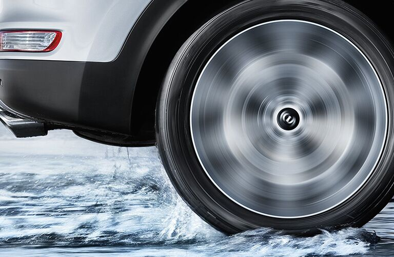 close up of wheel of 2018 kia sportage spinning on road with water and maintaining traction