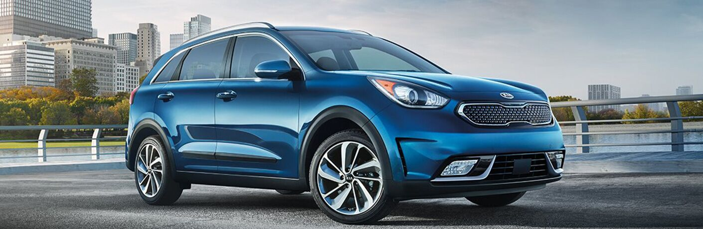 blue 2018 kia niro with city skyline in background