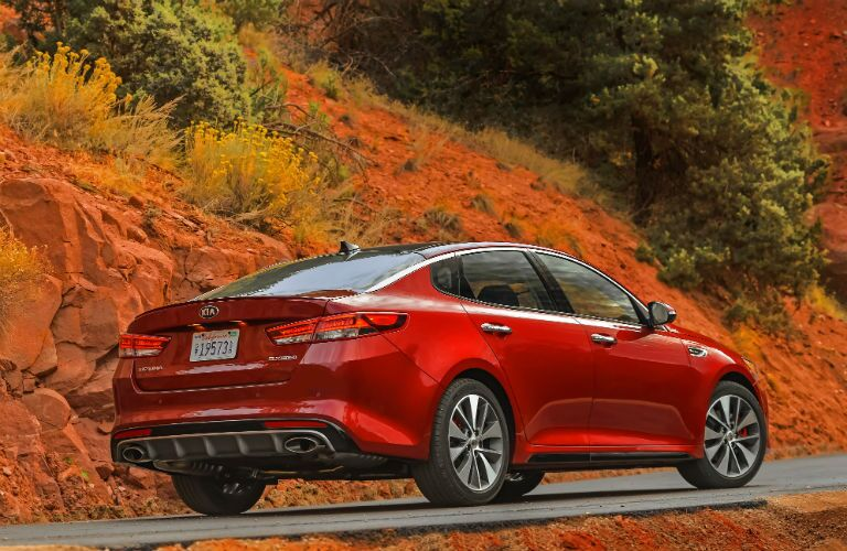 rear view of red 2018 kia optima driving on rocky road