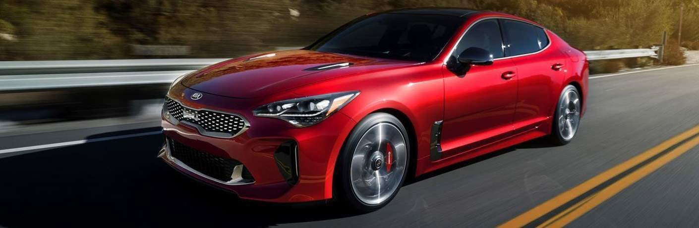 red 2018 kia stinger driving on single-lane highway