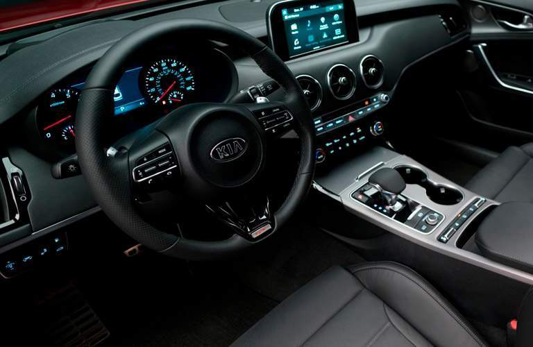 driver-side interior of 2018 kia stinger including steering wheel, dashboard, center console and center touch screen