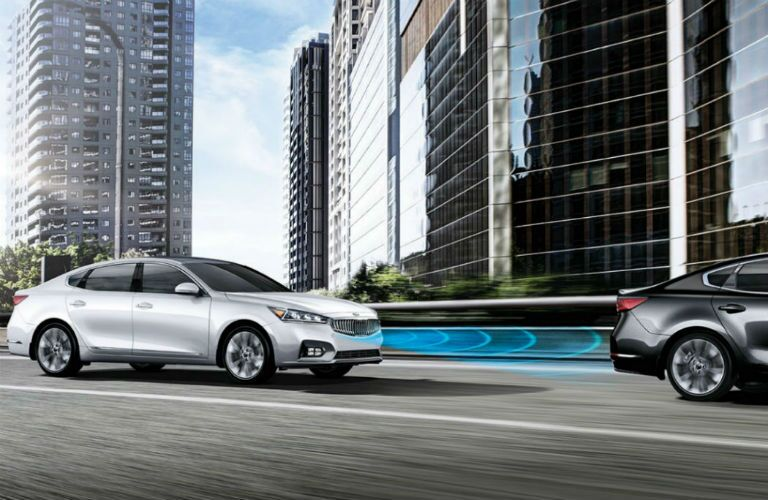 white 2018 kia cadenza driving in city with forward collision warning system