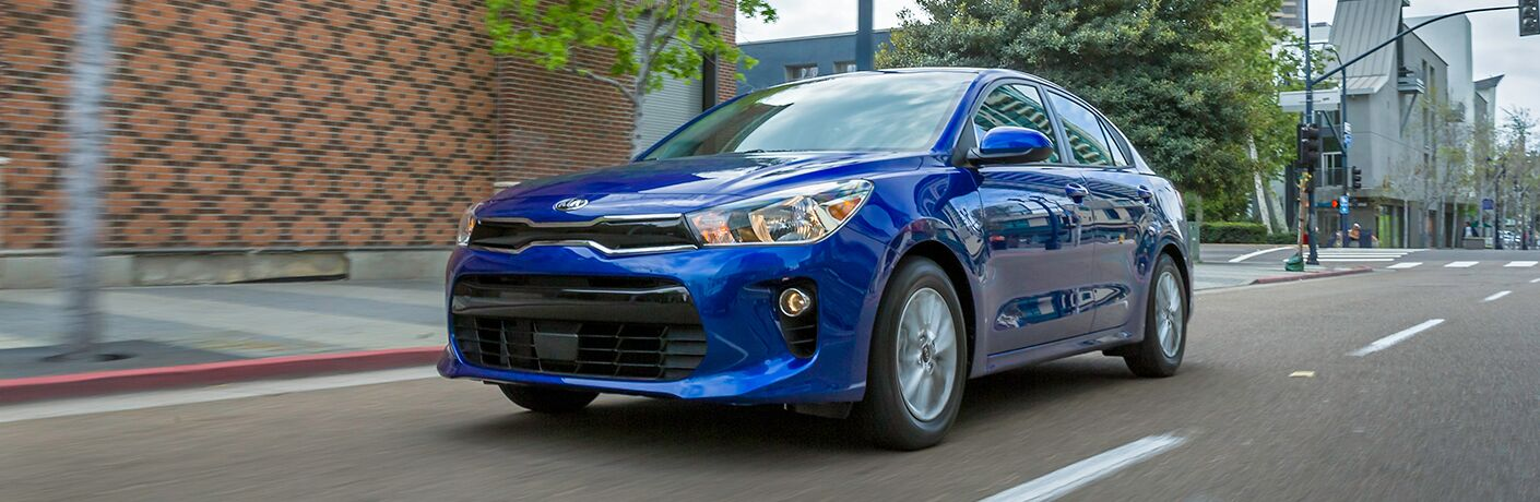 blue 2018 kia rio driving through downtown street